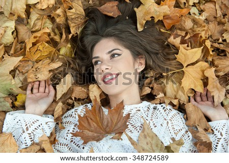 Nice girl covered with autumnal leaves. Young woman laying down on the ground covered by fall foliage in park. Beautiful sexy girl lying on autumn leaves. Young woman covered with golden autumn leaves