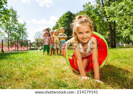 Nice girl crawling thought the tube in park - stock photo