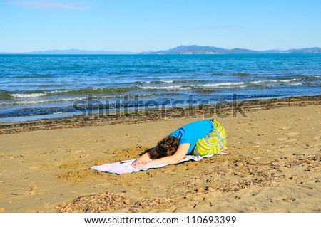 Nice girl doing yoga excercise on the beach at morning - stock photo