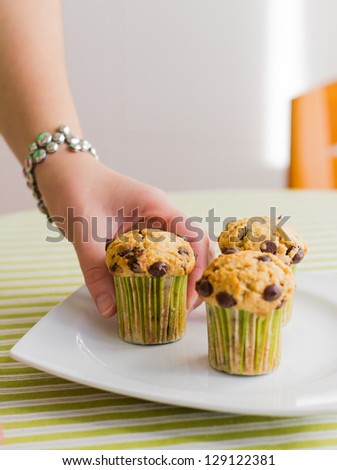 Nice girl hand taking delicious chocolate chip muffin at breakfast in green striped tablecloth - stock photo