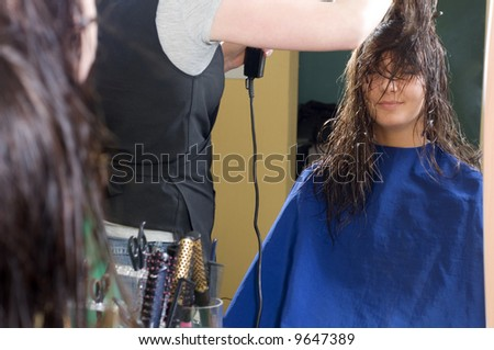 nice girl in a beauty salon while an hair stylist brush and dry her hair