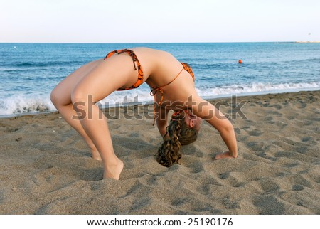 Nice girl making exercises on beach at evening