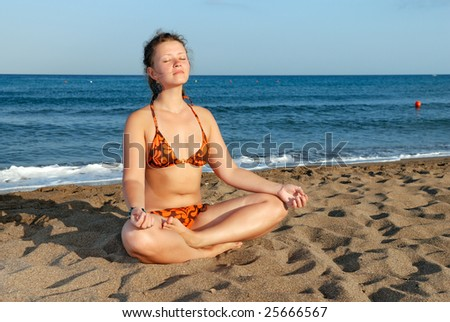 Nice girl meditating on the beach at evening