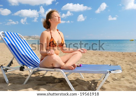 Nice girl meditating on the beach on the chair - stock photo