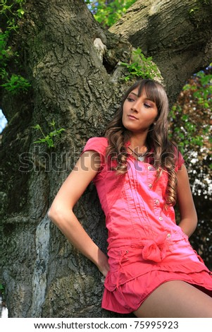 Nice girl standing leaning against the tree