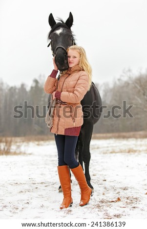 Nice girl with a horse in winter landscape - stock photo