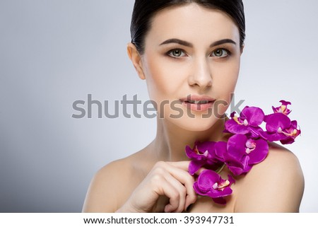 Nice girl with dark hair, big eyes, dark eyebrows and naked shoulders looking at camera and holding purple flower, a model with light nude make-up, smiling. - stock photo