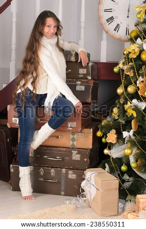 nice girl with long curly hair at pile of suitcases in christmas interior - stock photo
