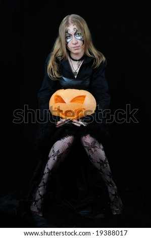 Nice girl with orange halloween pumpkin, on black background