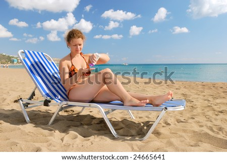 Nice girl with sun-protection cream on beach - stock photo