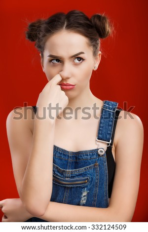 Nice girl, with top knot hairdo, wearing on denim jumpsuit, touching her nose on the red background, in studio, waist up - stock photo