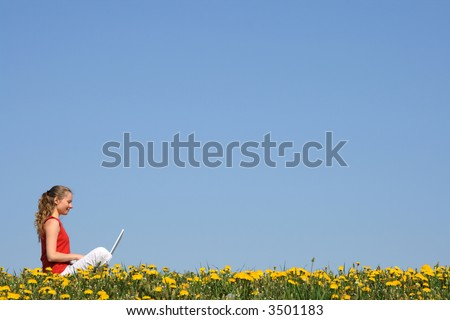 Nice girl working with laptop outdoors, in a flowering field. - stock photo