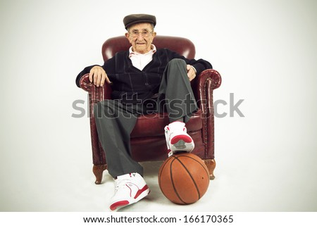 Nice grandfather sitting in a chair holding a basket ball and basketball shoes. - stock photo