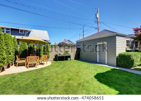 Nice green shed in the backyard of American craftsman house. Patio table set with thujas and well kept lawn. Northwest, USA