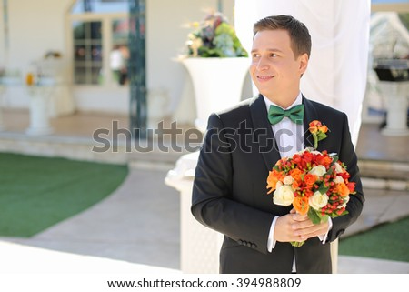 Nice groom portrait with bridal bouquet