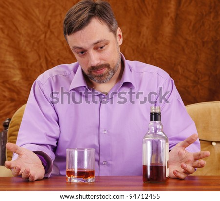 nice guy drinking whiskey at the table - stock photo