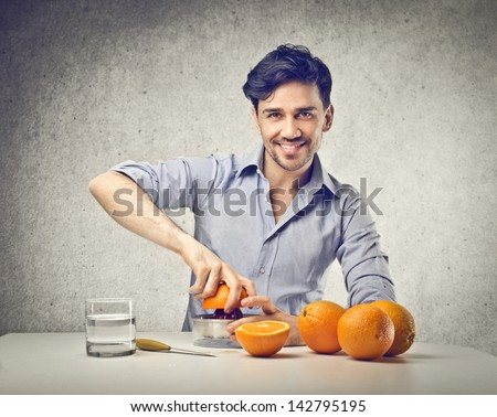 nice guy squeezes oranges - stock photo