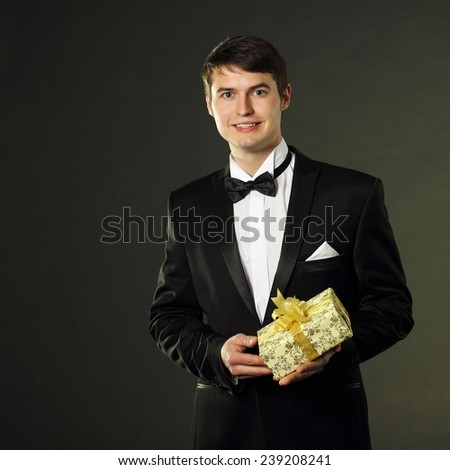 nice handsome man in a tuxedo gives a gift. On a black background. - stock photo