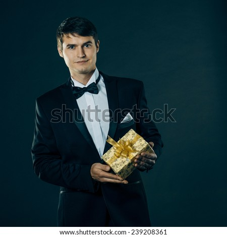 nice handsome man in a tuxedo gives a gift. On a black background. vintage toning - stock photo