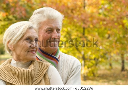 nice happy elderly couple in a autumn park - stock photo