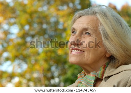 nice happy old woman on the autumn background - stock photo