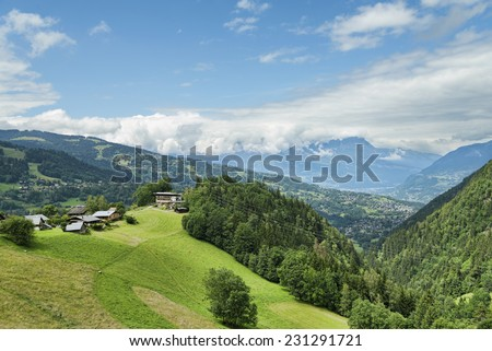 Nice houses on top of alpine hill - stock photo