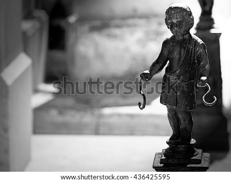 Nice image of a creepy sad baby statue with hooks in the hands. Unique dark style image. - stock photo