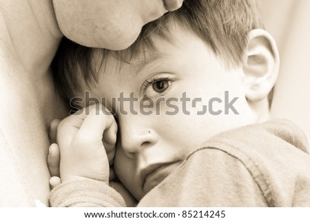 Nice image of a young upset boy cuddling his mum - stock photo