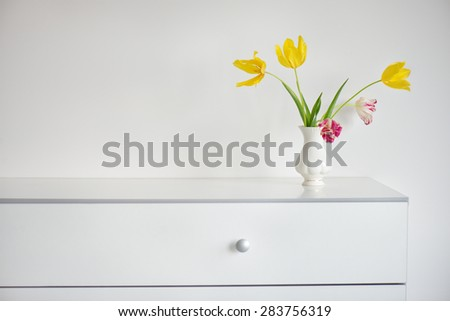 nice interior design scene with a white modern commode and a vase of yellow and pink tulips on a pale grey wall - stock photo