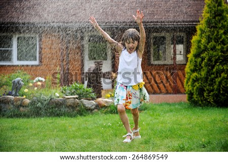 Nice kid girl with long hair has fun with garden sprinkler playing with water splashes in the backyard on a sunny hot summer  evening. - stock photo