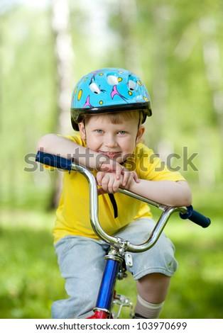 nice kid in helmet on bicycle - stock photo