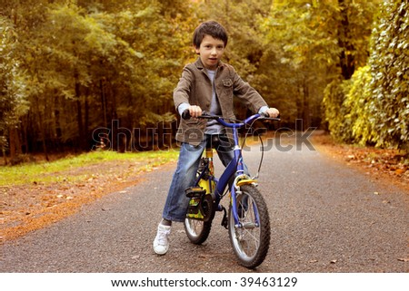 nice kid riding bike in a park - stock photo