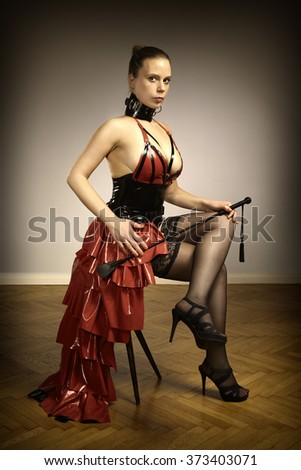 Nice lady in sexy latex apparel with crop - stock photo