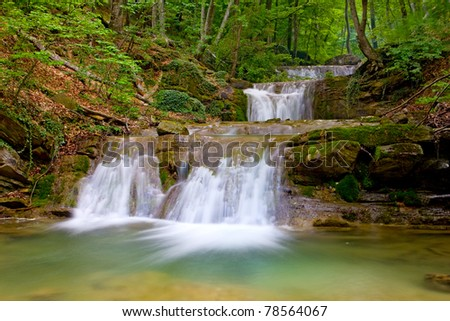 Nice landscape with waterfall in green forest - stock photo