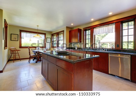 Nice large kitchen with cherry wood and island. - stock photo