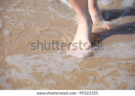 nice legs in water, nice pedicure red nail sand beach - stock photo