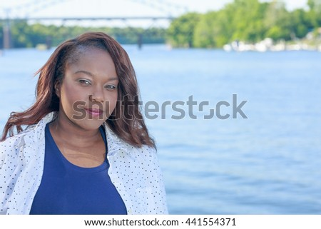 Nice lifestyle shot of a plus size african american woman outside in a casual outfit