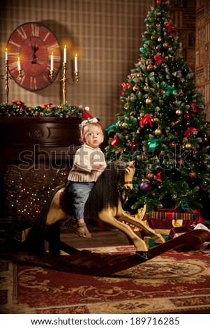 Nice little baby near the Christmas tree. Little boy celebrating Christmas. Cute smiling child with New Year gifts. Christmas Toddler riding a toy horse - stock photo