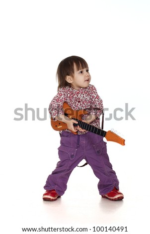 Nice little Caucasian girl plays with a guitar on a white background