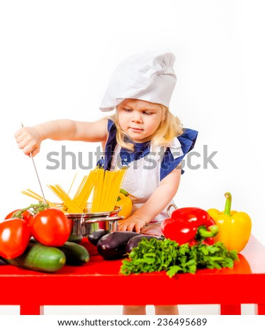 Nice little girl in white cap trying to cook