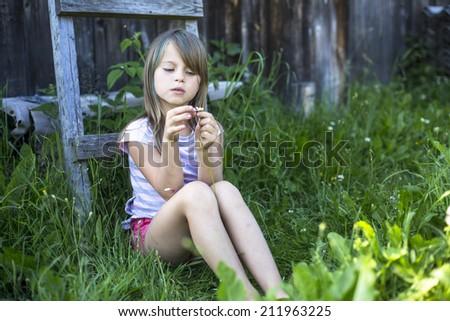 Nice little girl near a country house. - stock photo