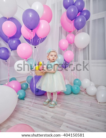 Nice little girl playing with balloons. The atmosphere of joy, fun, holiday. Birthday. - stock photo