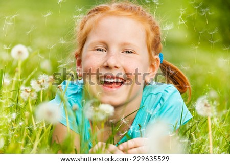 Nice little girl smiles while laying on a grass of a green meadow