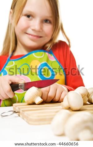 Nice little girl wearing apron slicing mushrooms - stock photo