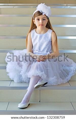 Nice little girl wearing white dress sitting on the steps - stock photo