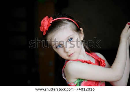 Nice little girl with big blue eyes in flower headband looks into the camera