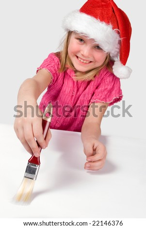 Nice little girl with red christmas hat painting with brush. Focus on brush and hand - stock photo