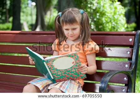 Nice little studious girl preschooler is reading open book and sitting on the red plaid on green grass in summer park - stock photo