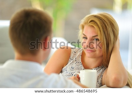 Nice long-haired young blonde woman sitting on a couch propped her head with one hand and holding a mug of delicious tea in another hand, in love looking at her husband