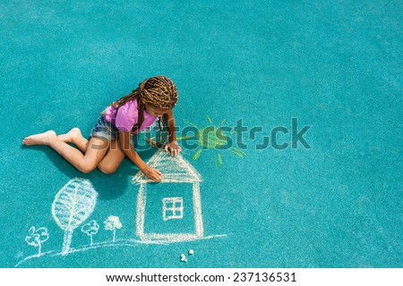 Nice looking black girl drawing house sun and trees with chalk on playground  - stock photo